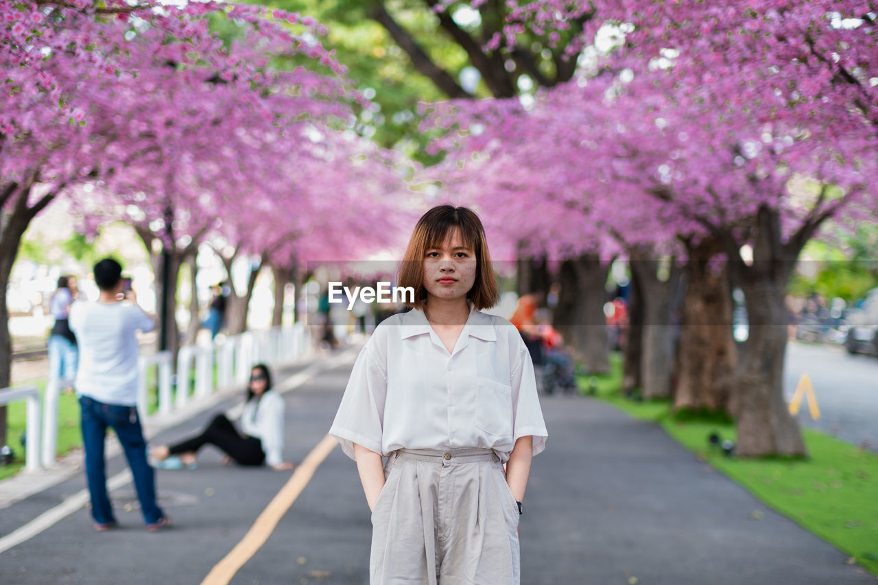 Portrait of woman standing by pink flower tree