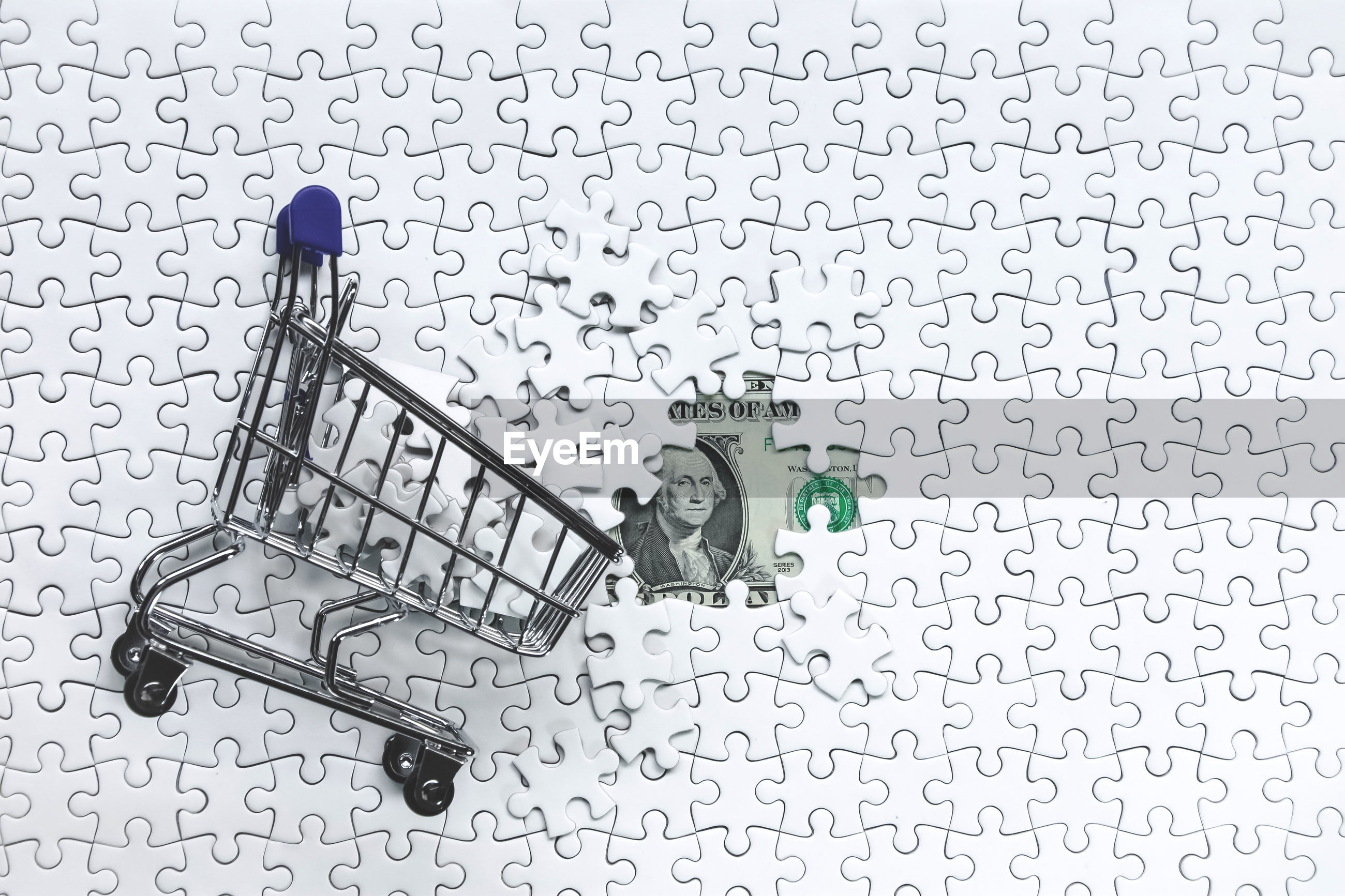 Directly above shot of small shopping cart on jigsaw puzzle