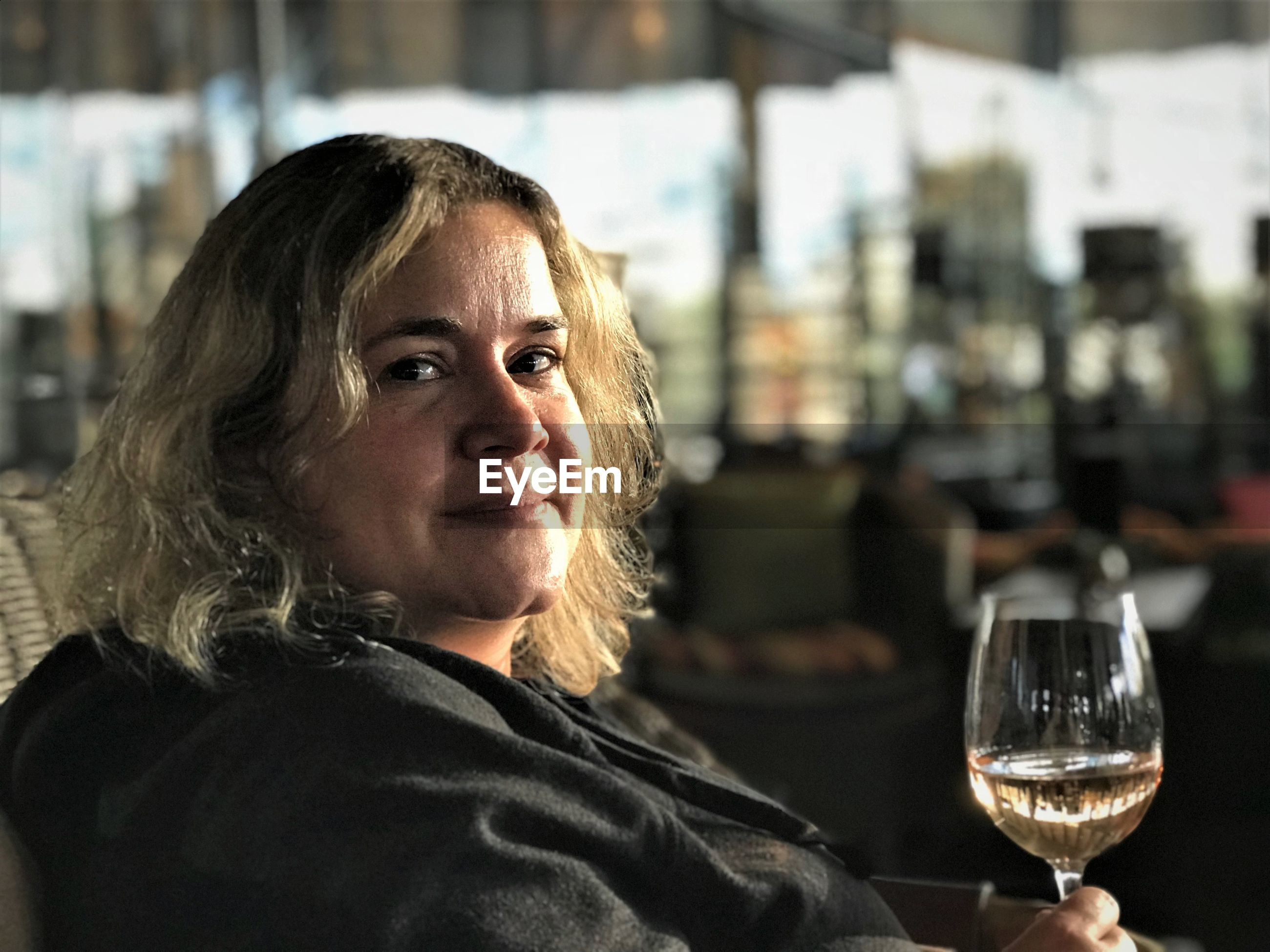 Portrait of mid adult woman having wine while sitting in restaurant