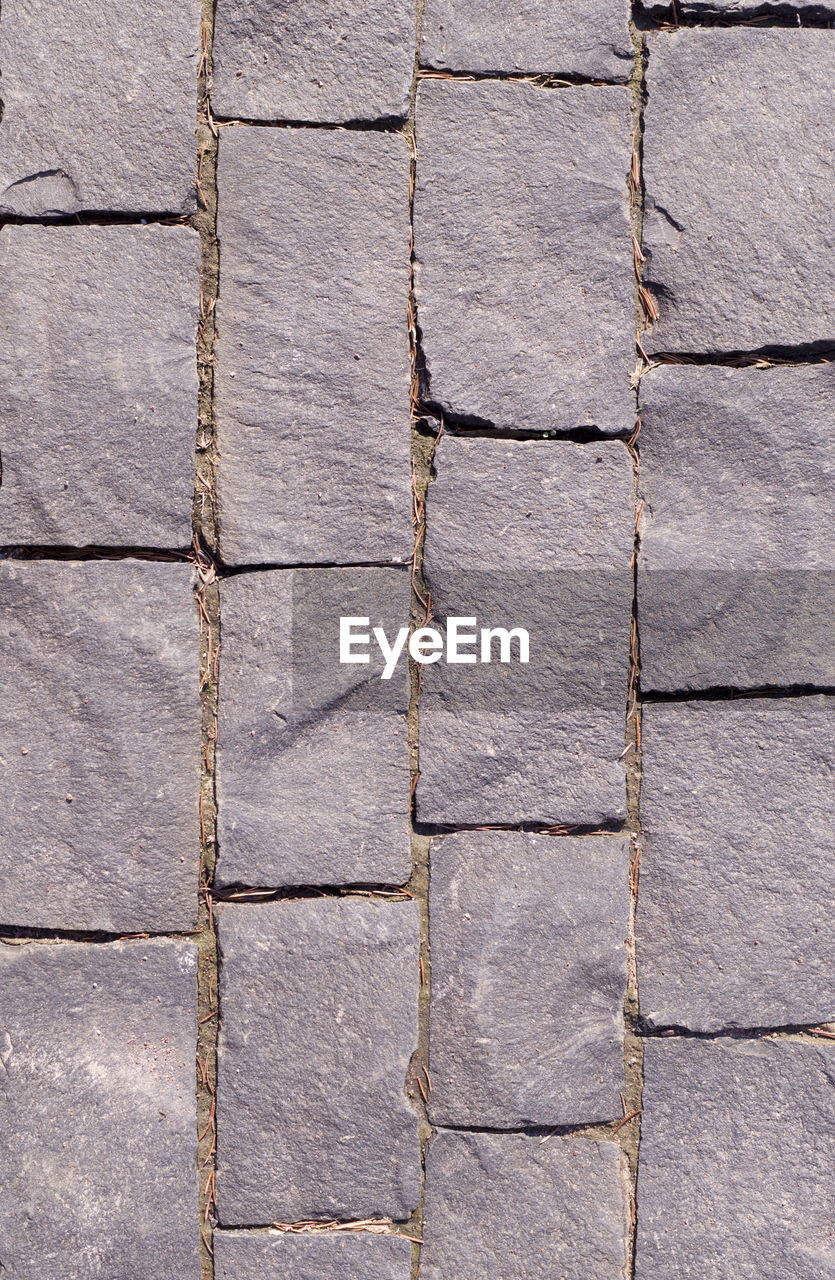 full frame, backgrounds, pattern, textured, built structure, no people, architecture, wall - building feature, wall, day, rough, footpath, close-up, paving stone, repetition, brick, gray, outdoors, in a row, stone, stone wall, concrete