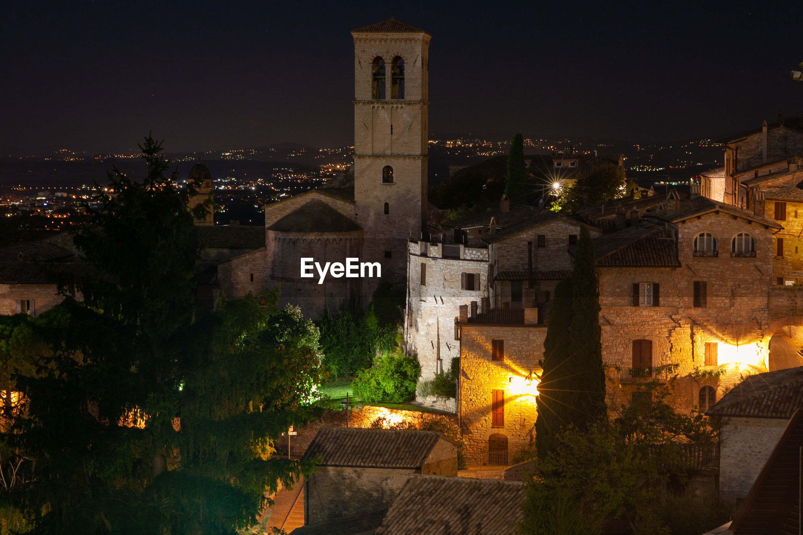 Night assisi cityscape, umbria, italy, with lights from spoleto plain on background
