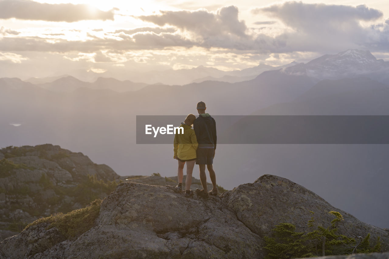 mountain, beauty in nature, leisure activity, scenics - nature, sky, standing, cloud - sky, non-urban scene, rock, solid, real people, lifestyles, rock - object, tranquil scene, mountain range, rear view, nature, idyllic, trip, tranquility, outdoors, mountain peak, looking at view