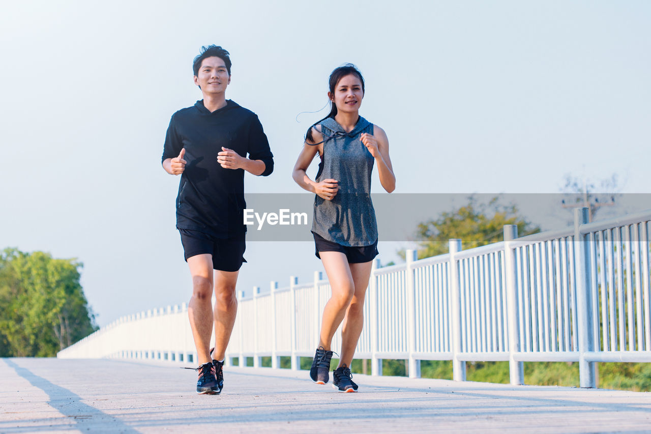 real people, lifestyles, two people, togetherness, casual clothing, full length, front view, architecture, leisure activity, railing, people, young adult, nature, day, focus on foreground, sky, young men, young women, women, bonding, outdoors, shorts