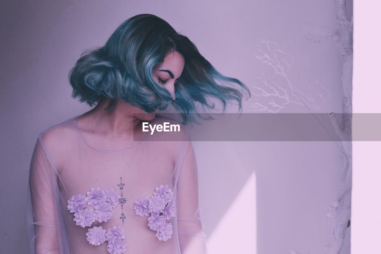 Sensuous woman wearing transparent while tossing dyed hair against white wall