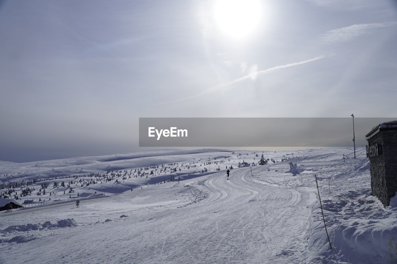winter, cold temperature, snow, sky, scenics - nature, beauty in nature, sun, nature, sunlight, non-urban scene, sunbeam, tranquility, environment, cloud - sky, tranquil scene, landscape, day, white color, covering, lens flare, no people, outdoors, snowcapped mountain, bright, powder snow