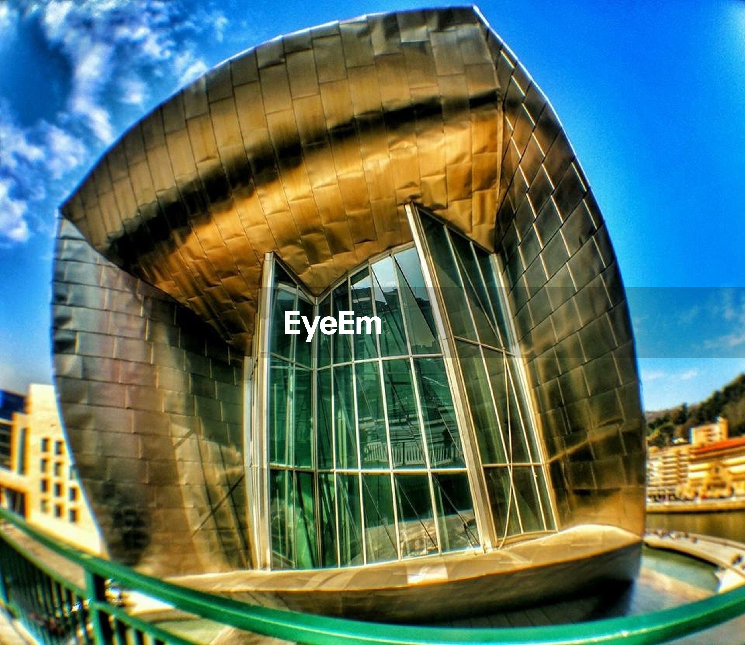 architecture, built structure, building exterior, blue, low angle view, city, sky, glass - material, modern, famous place, travel destinations, building, reflection, travel, fish-eye lens, outdoors, no people, day, capital cities, cloud - sky