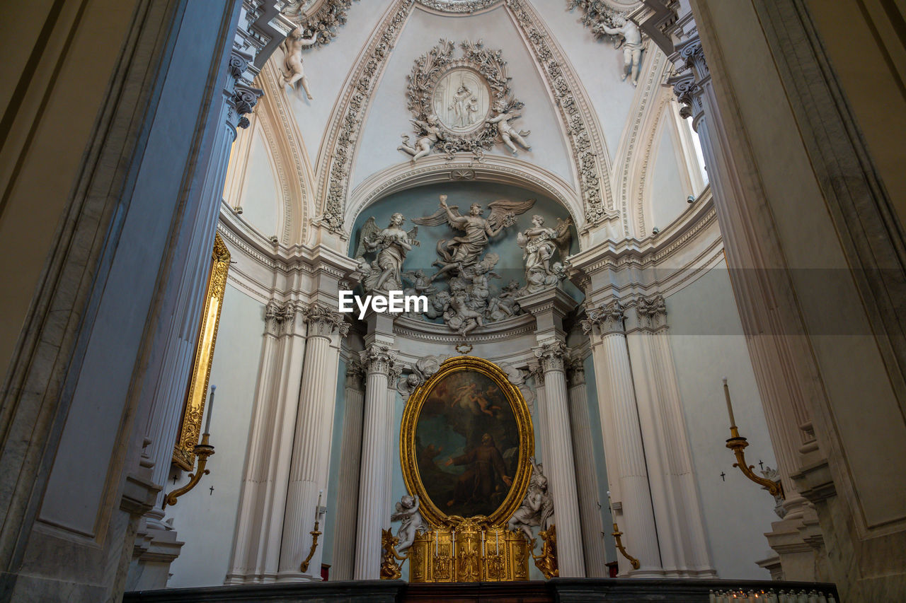 place of worship, belief, spirituality, low angle view, architecture, religion, representation, built structure, building, human representation, no people, building exterior, art and craft, history, the past, sculpture, ceiling, ornate, architectural column