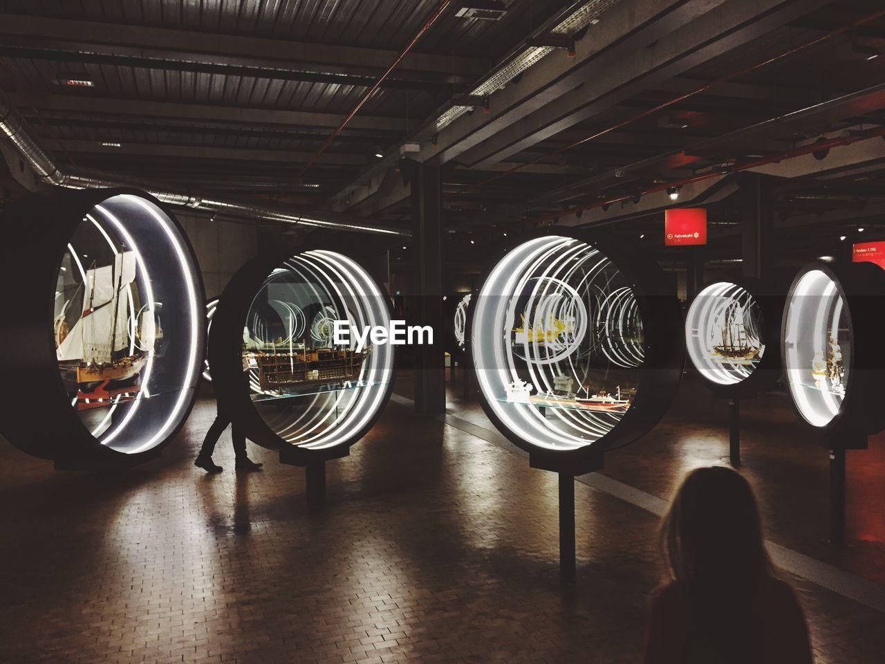 indoors, circle, illuminated, real people, technology, close-up, laundromat, day