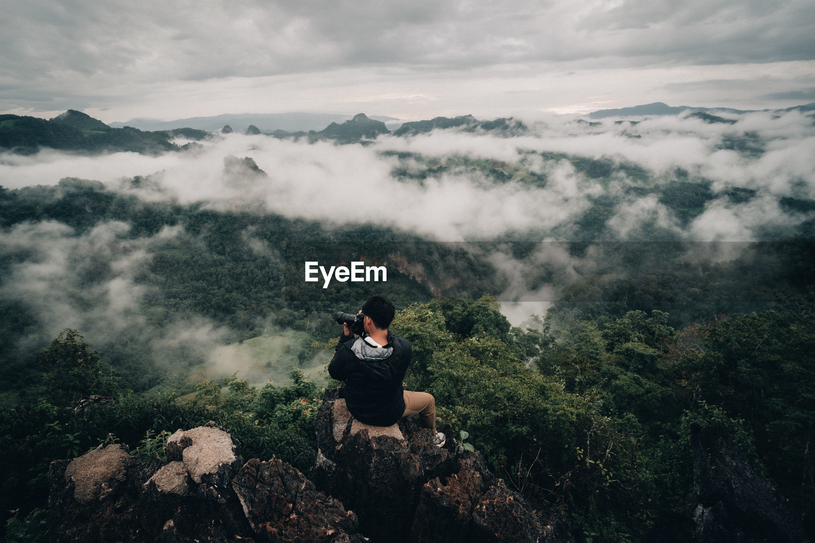 MAN SITTING ON MOUNTAIN LOOKING AT VIEW