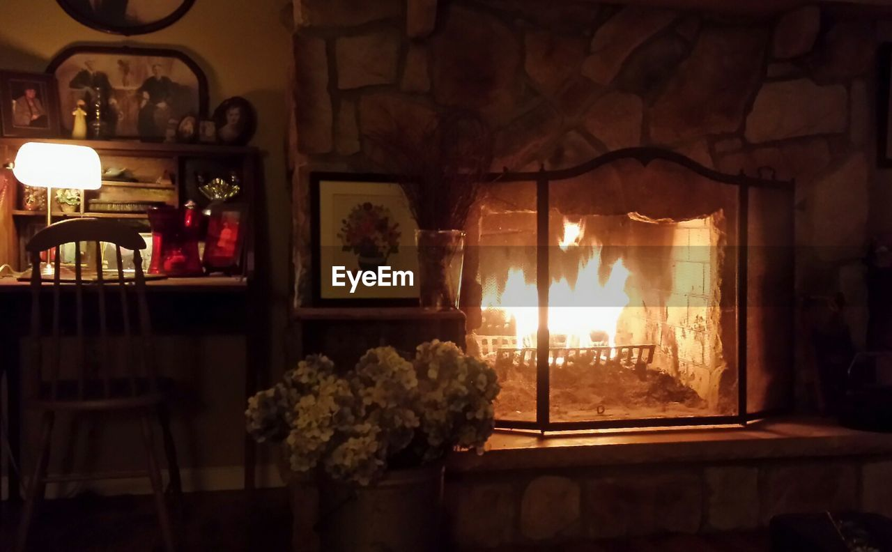 indoors, burning, flame, home interior, no people, heat - temperature, night, illuminated, fireplace, window, flower, close-up