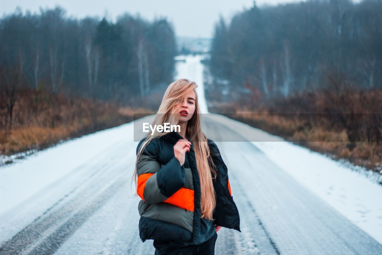 Portrait Of Young Woman Standing On Snow Covered Road