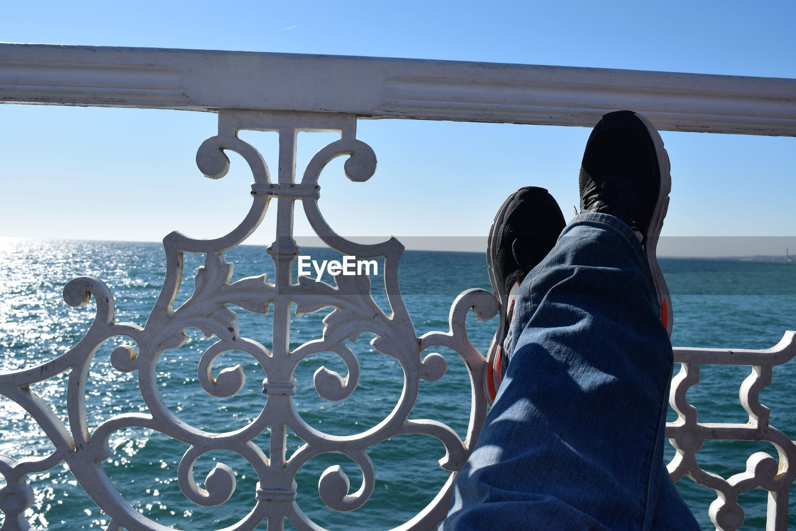 Low section of person with feet up on railing against sea