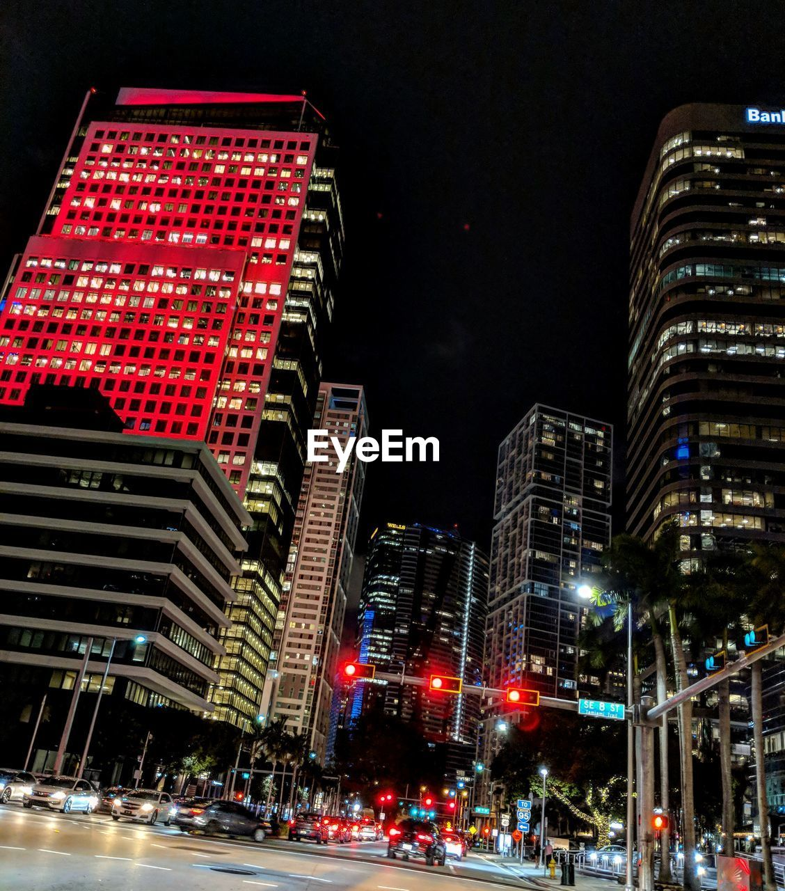 illuminated, architecture, night, building exterior, built structure, city, building, city life, tall - high, transportation, sky, mode of transportation, office building exterior, low angle view, modern, nature, city street, motion, street, cityscape, skyscraper, outdoors, nightlife