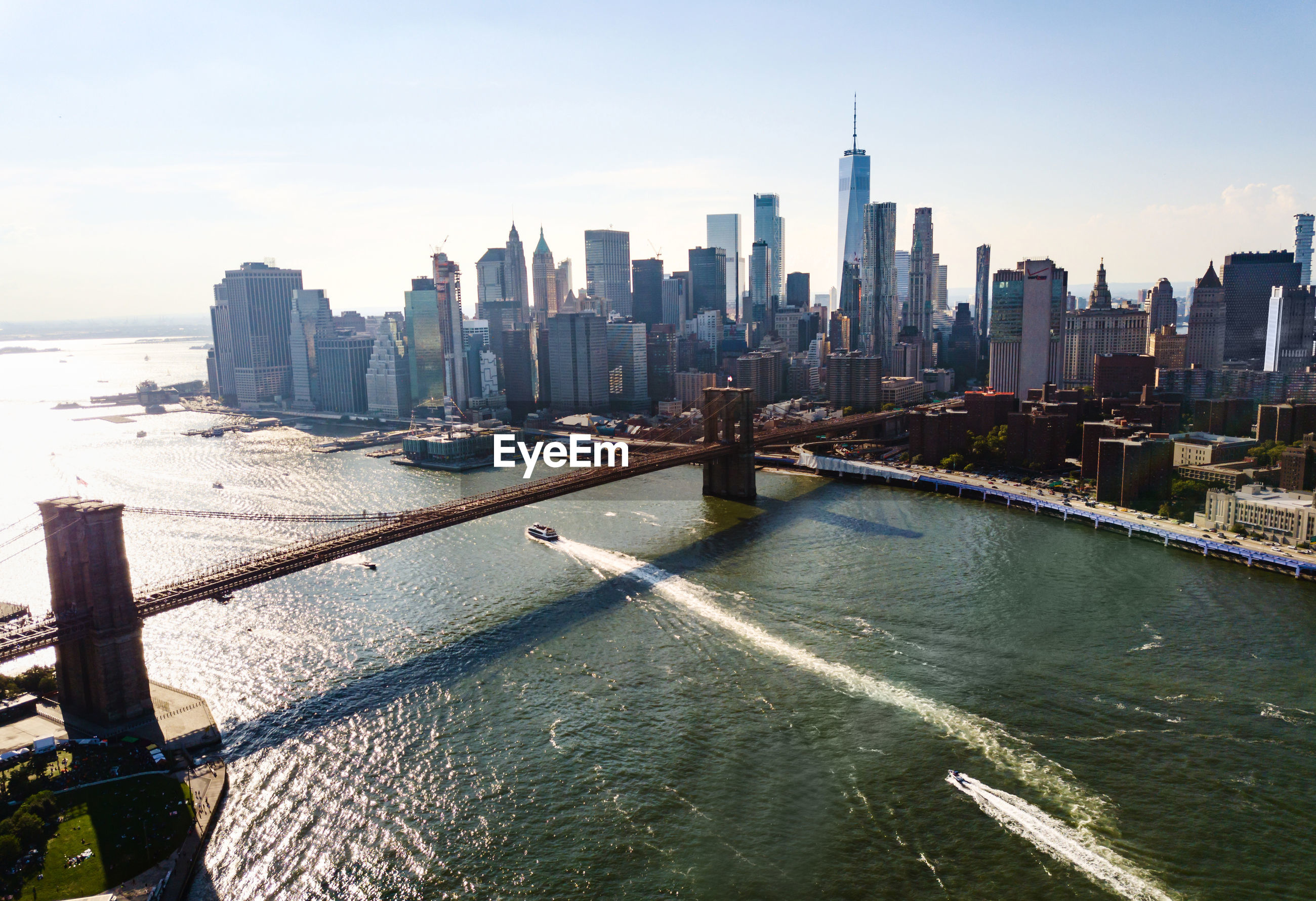 Aerial view of brooklyn bridge over river in city against sky