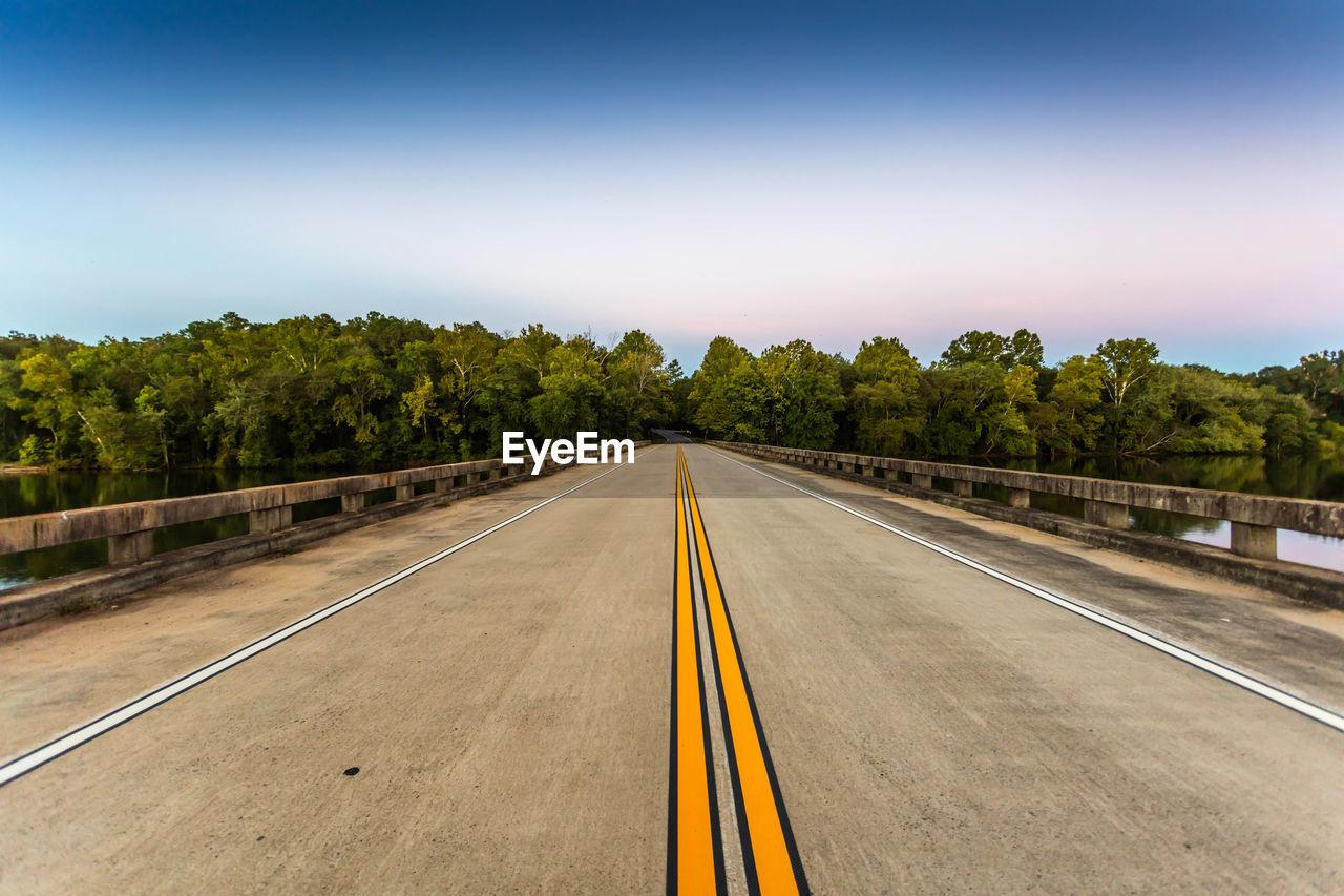 Empty Bridge Leading Towards Trees Against Sky