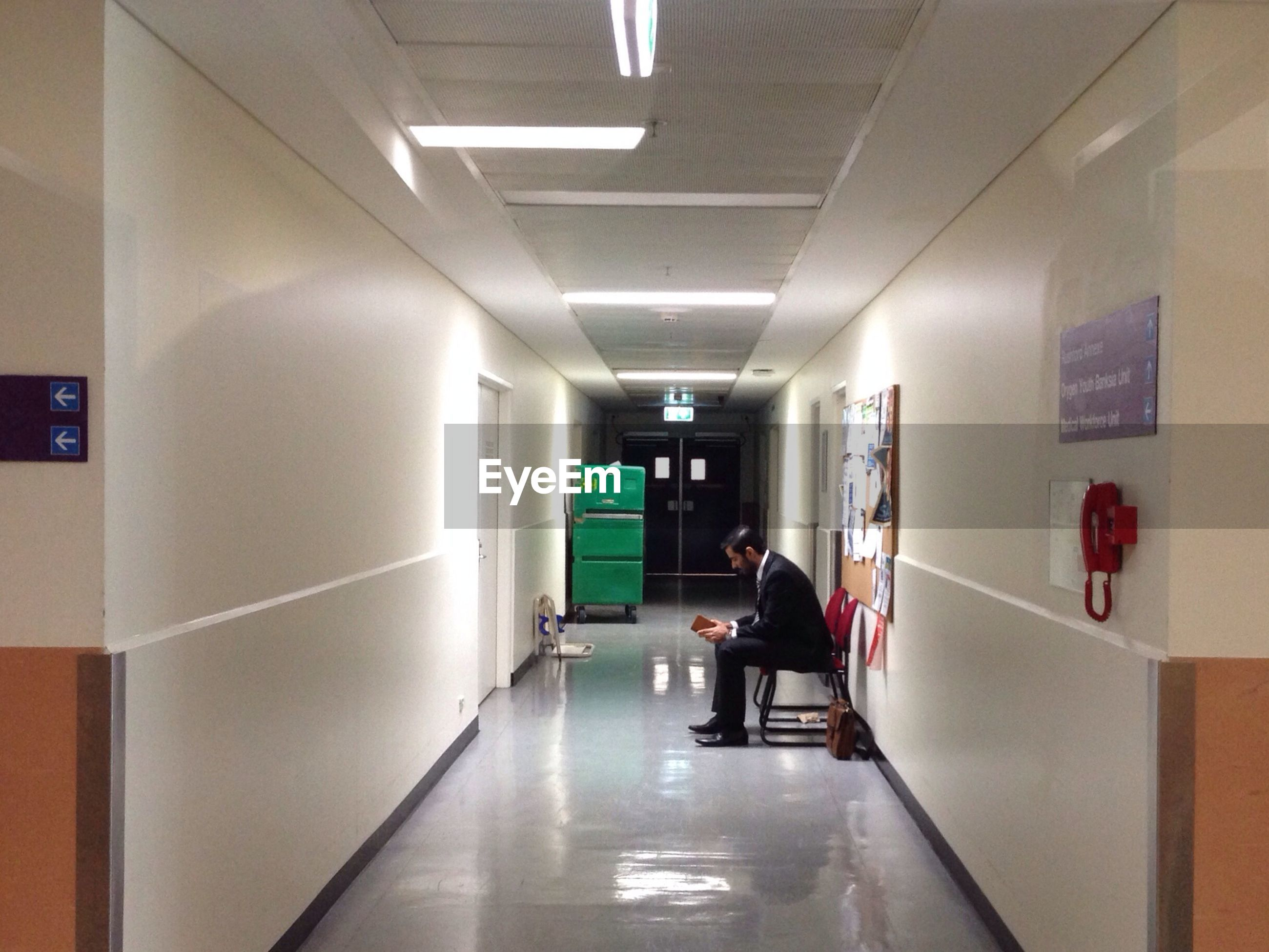 indoors, men, lifestyles, walking, full length, rear view, illuminated, architecture, corridor, built structure, person, leisure activity, the way forward, flooring, wall - building feature, communication, lighting equipment