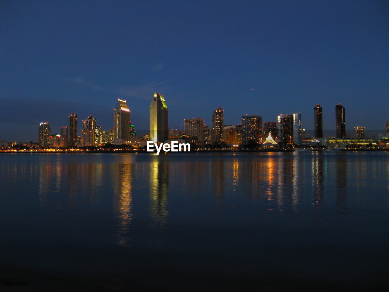 architecture, built structure, skyscraper, building exterior, reflection, cityscape, city, illuminated, waterfront, urban skyline, sky, no people, travel destinations, modern, night, water, outdoors