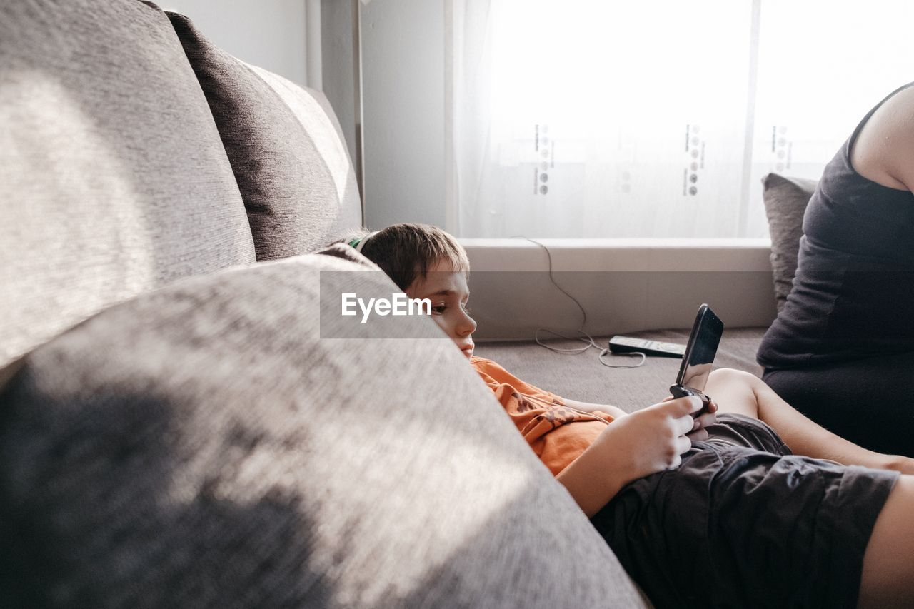 Boy Using Mobile Phone At Home