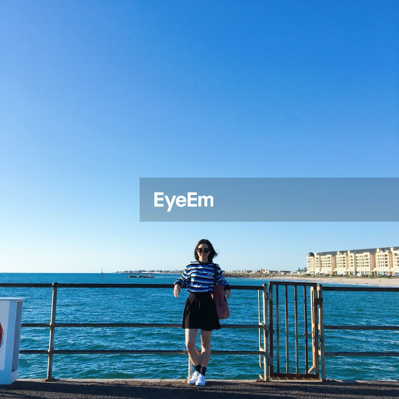 sky, water, clear sky, one person, copy space, sea, blue, real people, standing, front view, lifestyles, railing, leisure activity, casual clothing, nature, day, young adult, portrait, outdoors