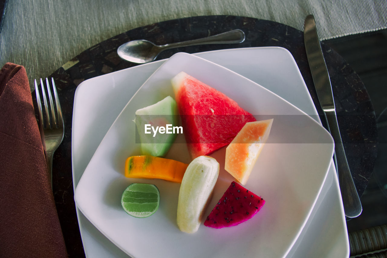 food, food and drink, plate, freshness, healthy eating, slice, kitchen utensil, table, wellbeing, still life, no people, eating utensil, indoors, high angle view, ready-to-eat, fruit, watermelon, sweet food, close-up, indulgence, melon, tray, breakfast, temptation
