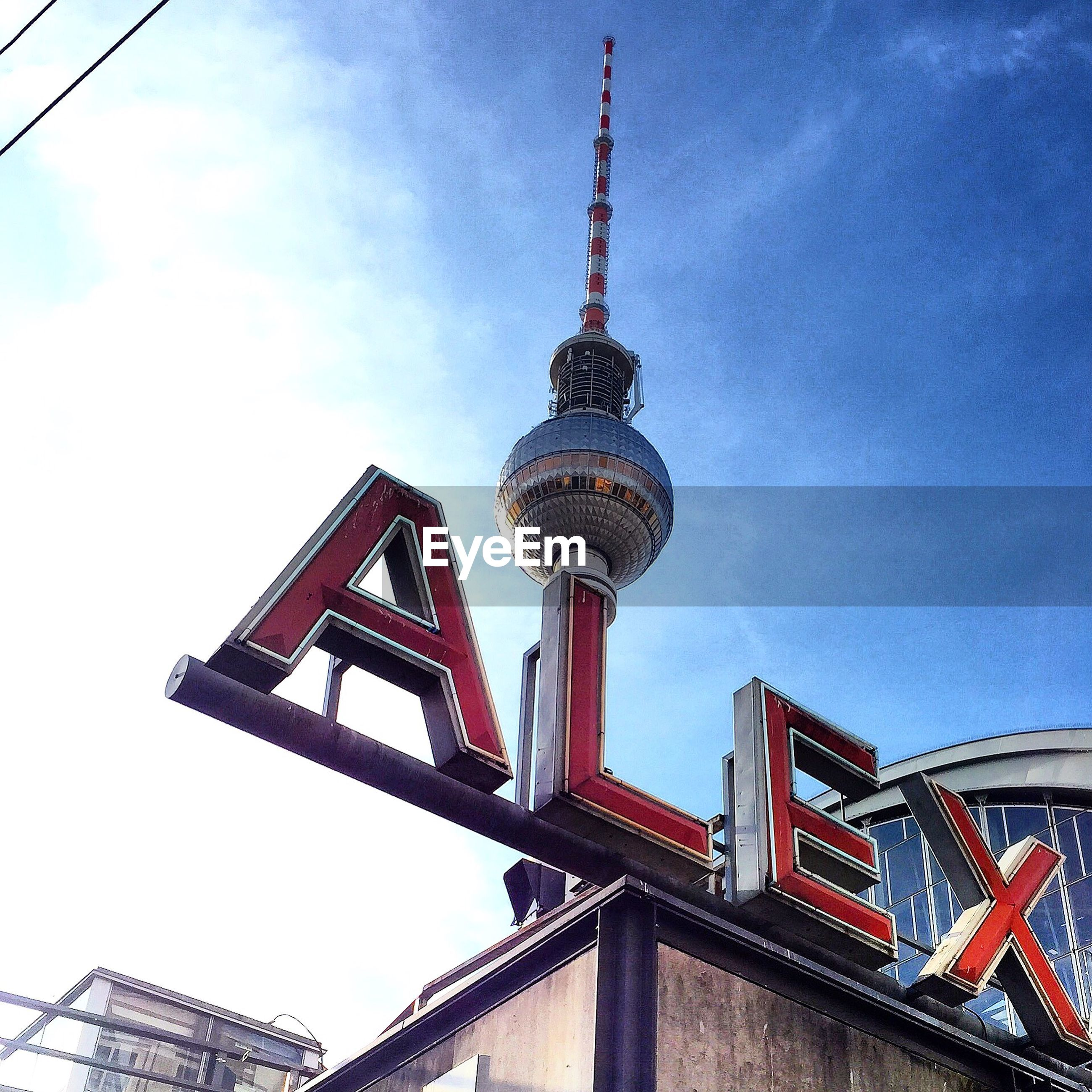 Low angle view of text and fernsehturm against blue sky