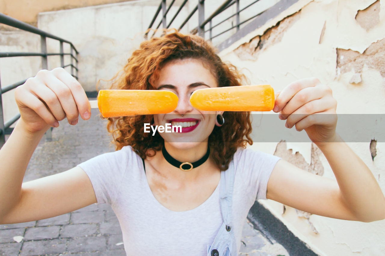 Close-Up Of Woman Smiling While Holding Orange Popsicles On Footpath