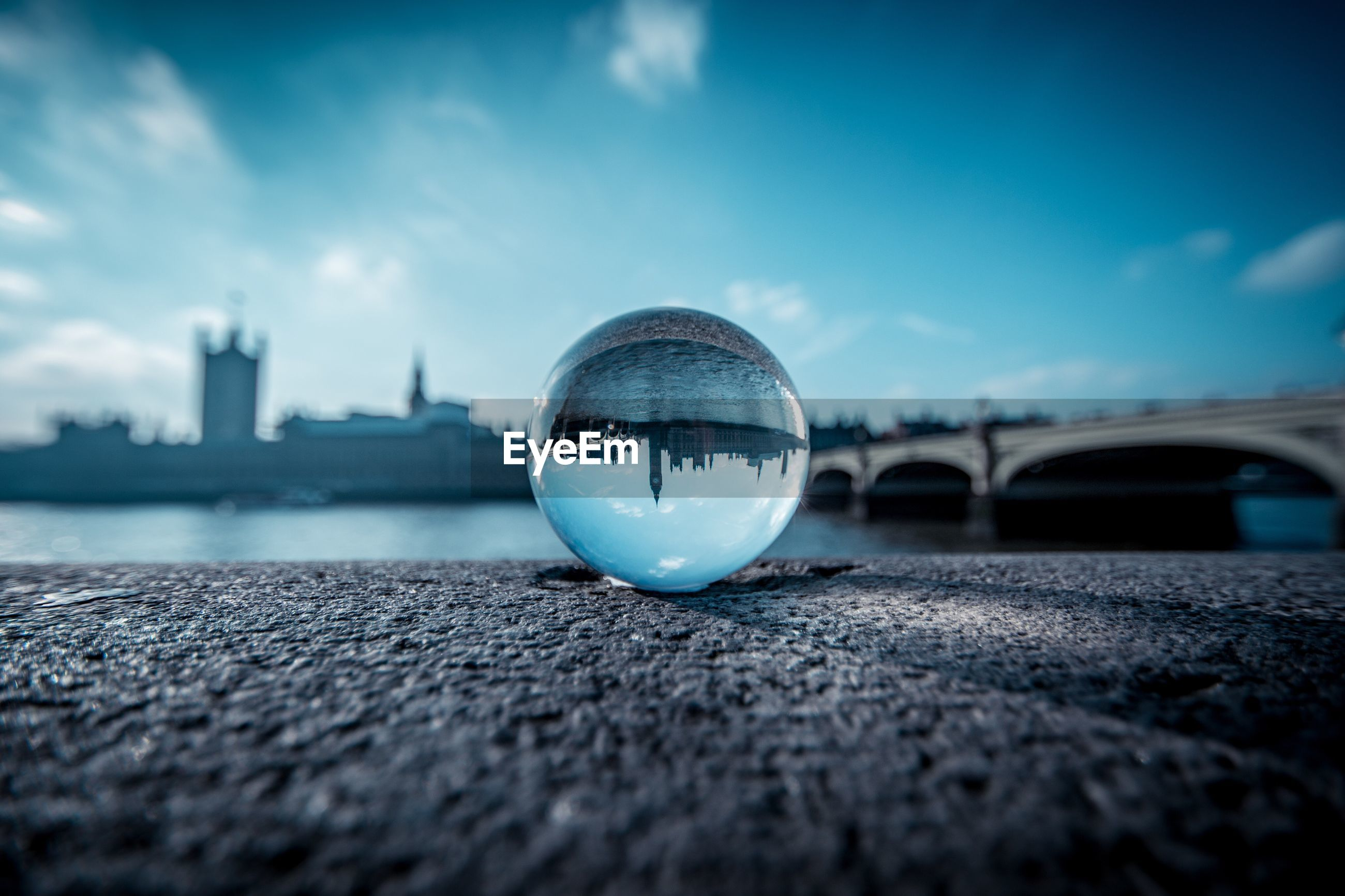 View of london through crystal ball against blue sky