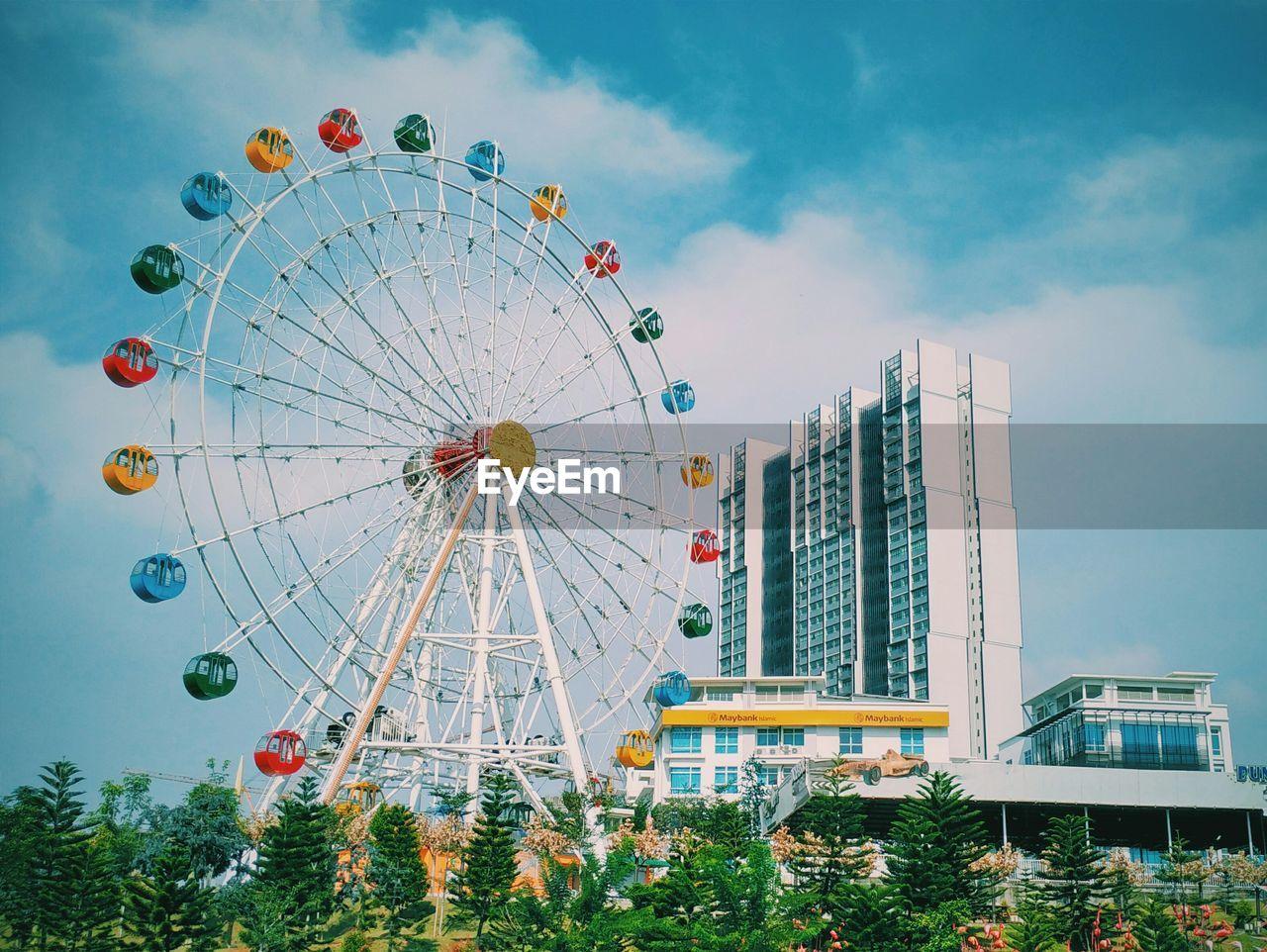 amusement park, ferris wheel, arts culture and entertainment, low angle view, sky, built structure, amusement park ride, architecture, building exterior, no people, day, big wheel, cloud - sky, outdoors, tree, city