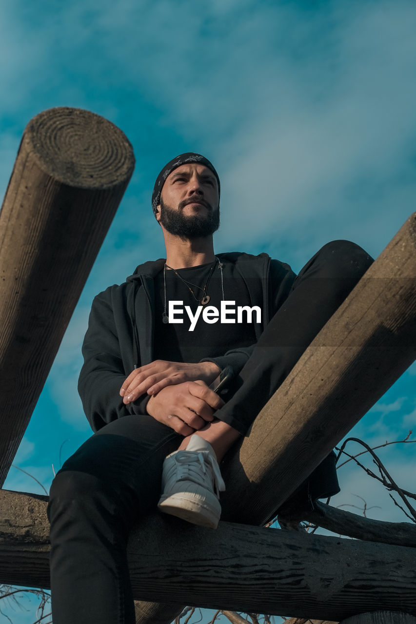 real people, one person, wood - material, sitting, casual clothing, sky, front view, men, young adult, lifestyles, young men, three quarter length, nature, leisure activity, seat, full length, focus on foreground, males, outdoors
