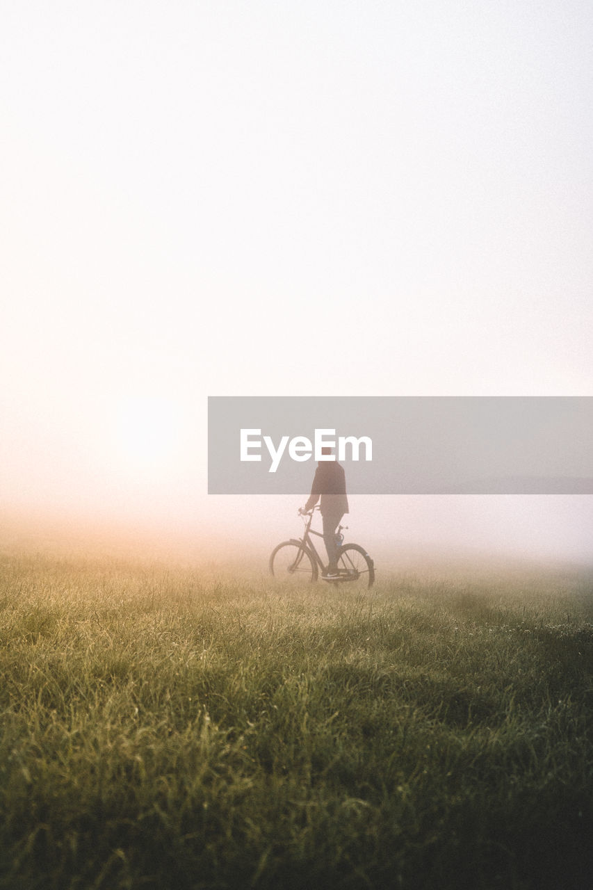 Full length of man with bicycle on field during foggy weather