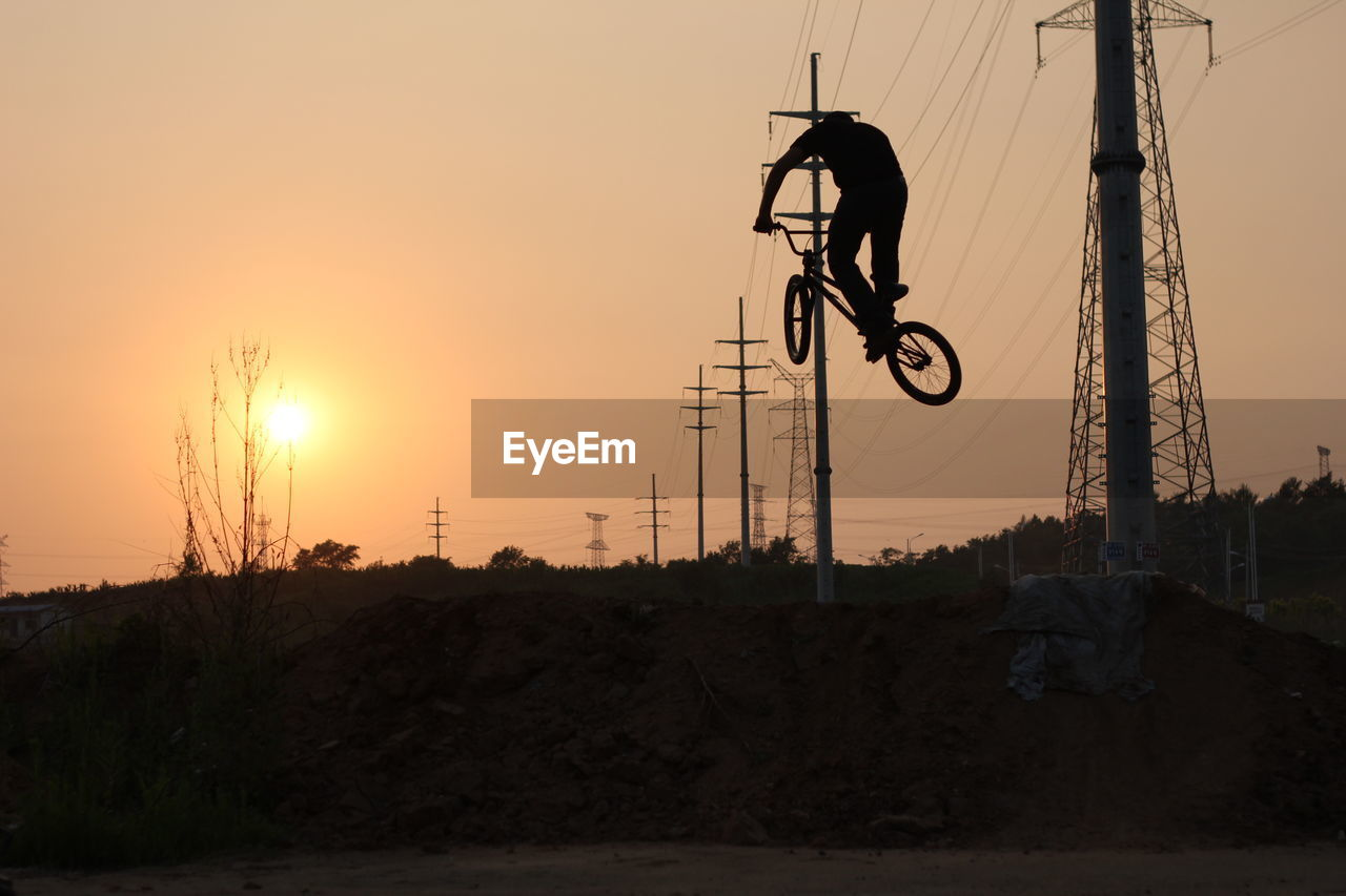 sunset, real people, one person, transportation, silhouette, leisure activity, men, outdoors, land vehicle, sky, skill, lifestyles, adventure, extreme sports, full length, stunt, electricity pylon, nature, competitive sport, motocross, biker, day, people