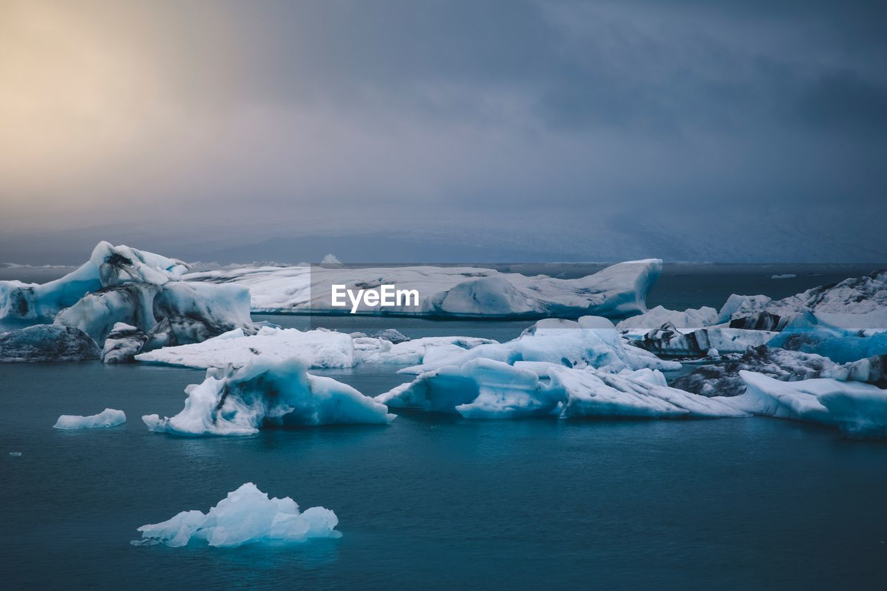 ice, cold temperature, glacier, water, iceberg, frozen, tranquil scene, sky, tranquility, scenics - nature, environment, beauty in nature, winter, landscape, waterfront, nature, cloud - sky, idyllic, snow, no people, floating on water, melting, lagoon
