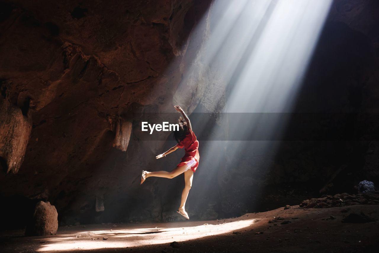 Carefree teenage girl dancing in cave