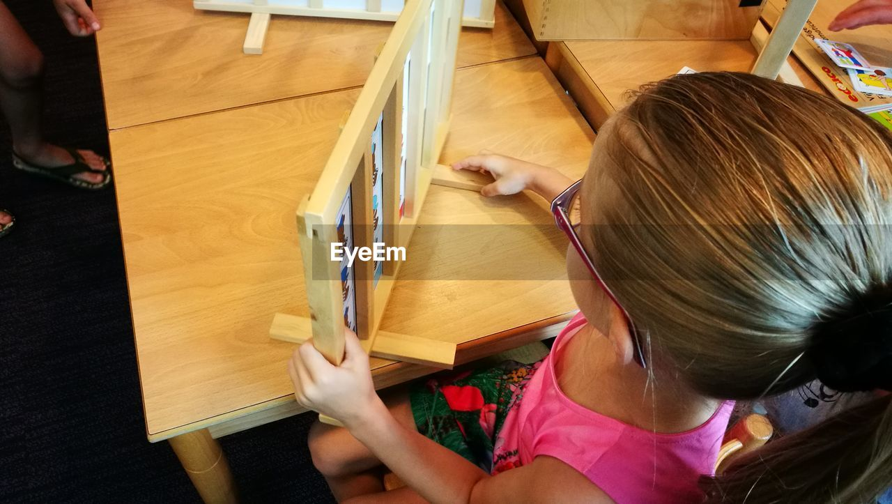 Girl reading wooden educational chart at table