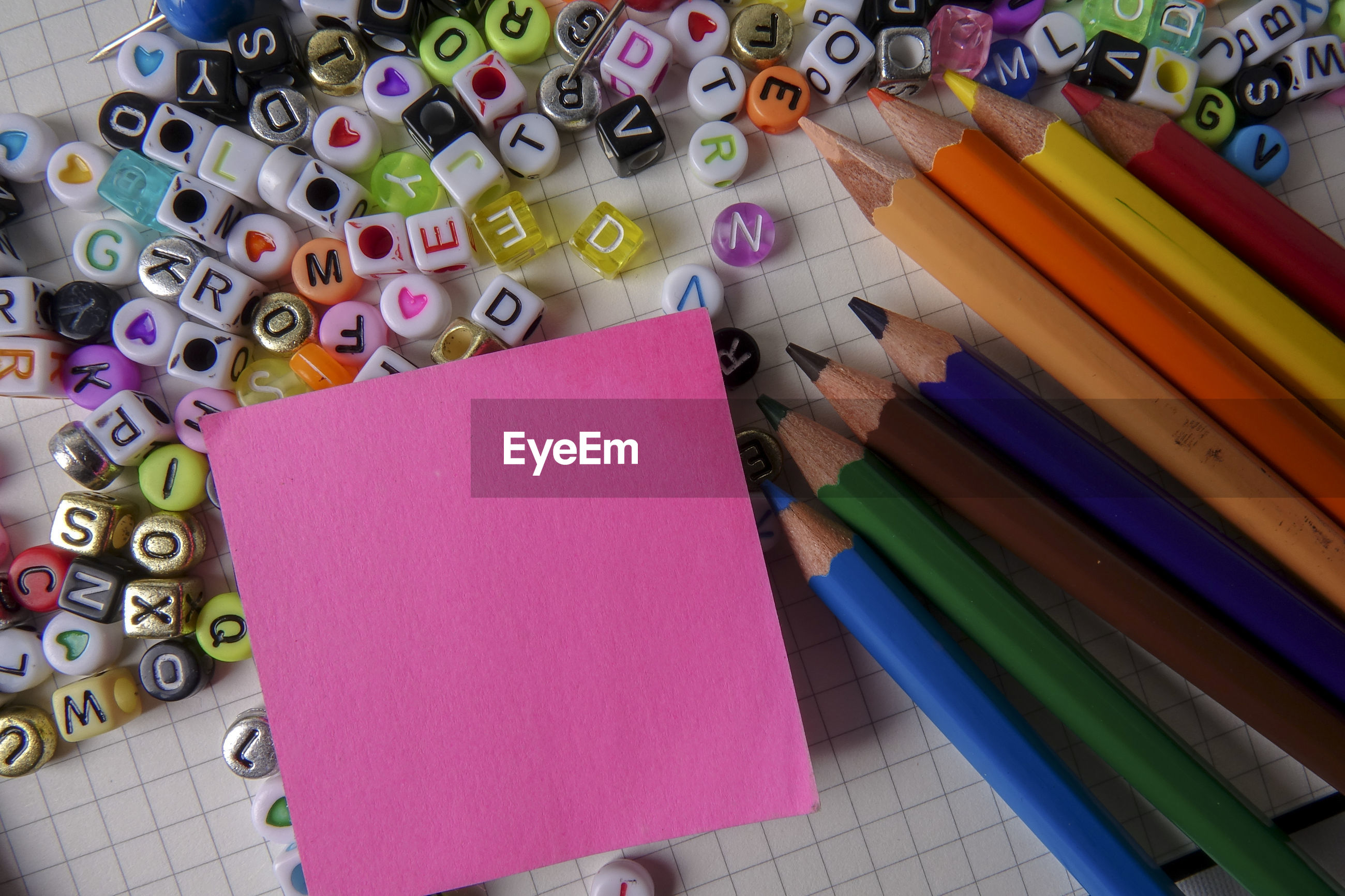 Directly above shot of alphabet beads with school supplies and easel on paper