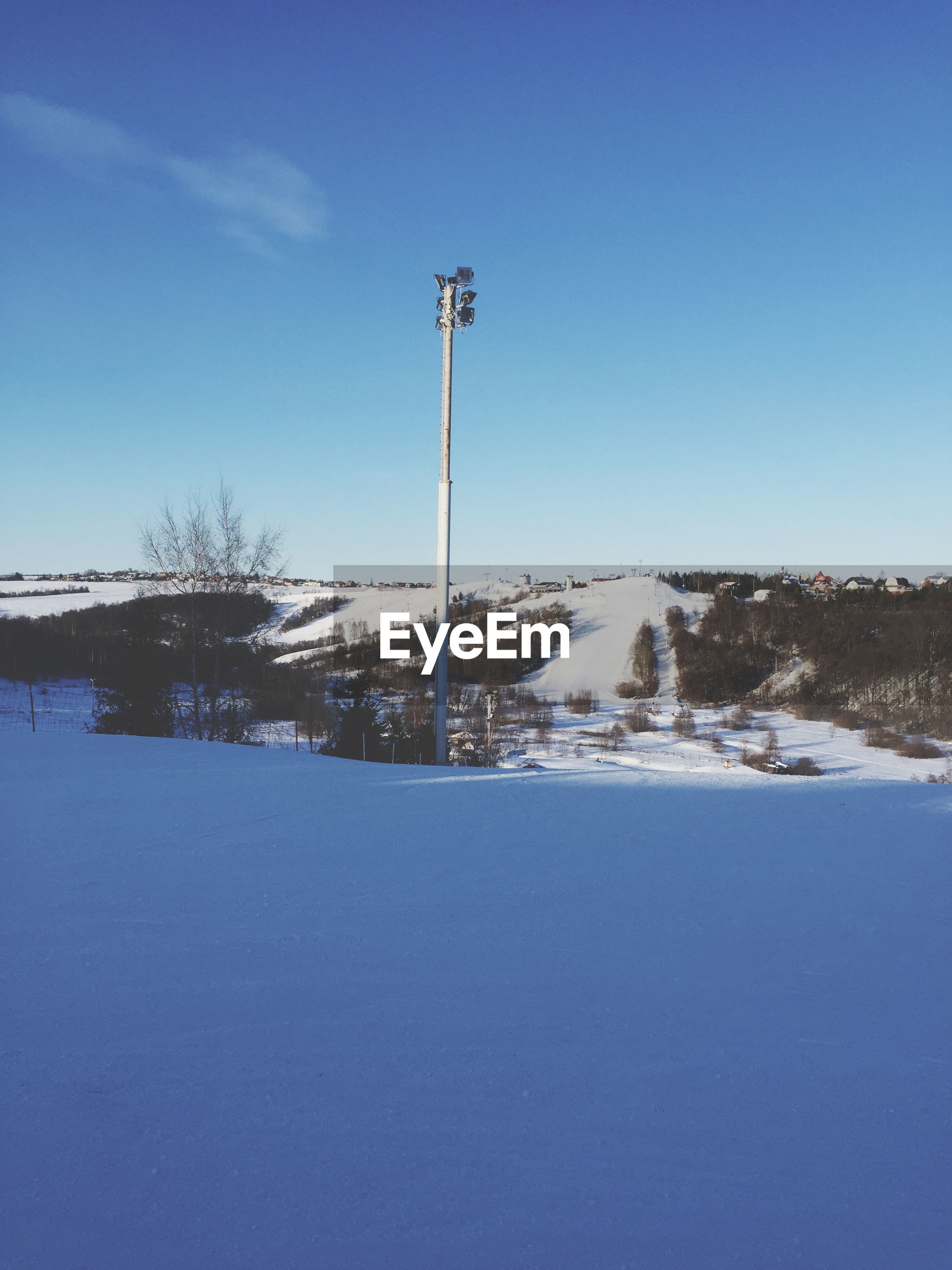Snow covered land against blue sky