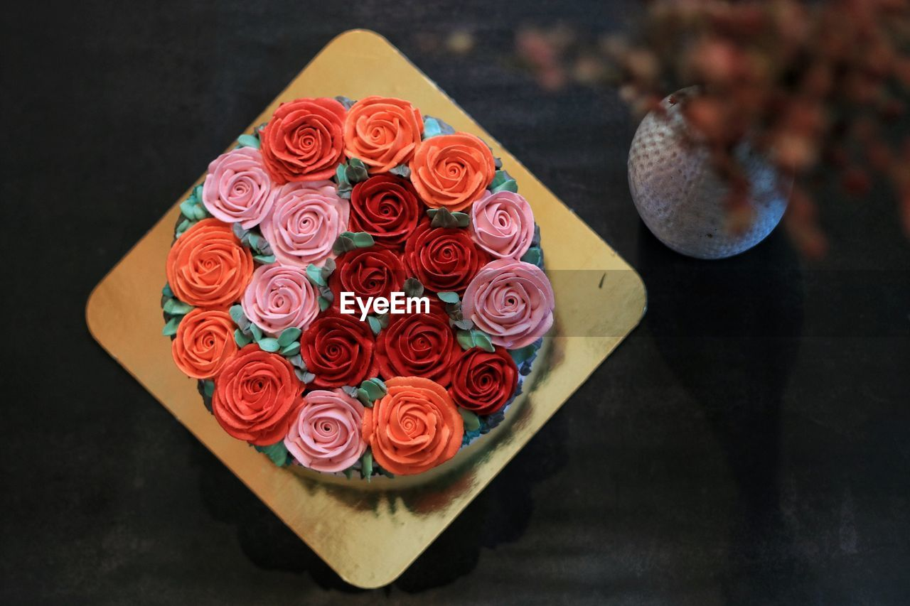 HIGH ANGLE VIEW OF MULTI COLORED CAKE ON TABLE