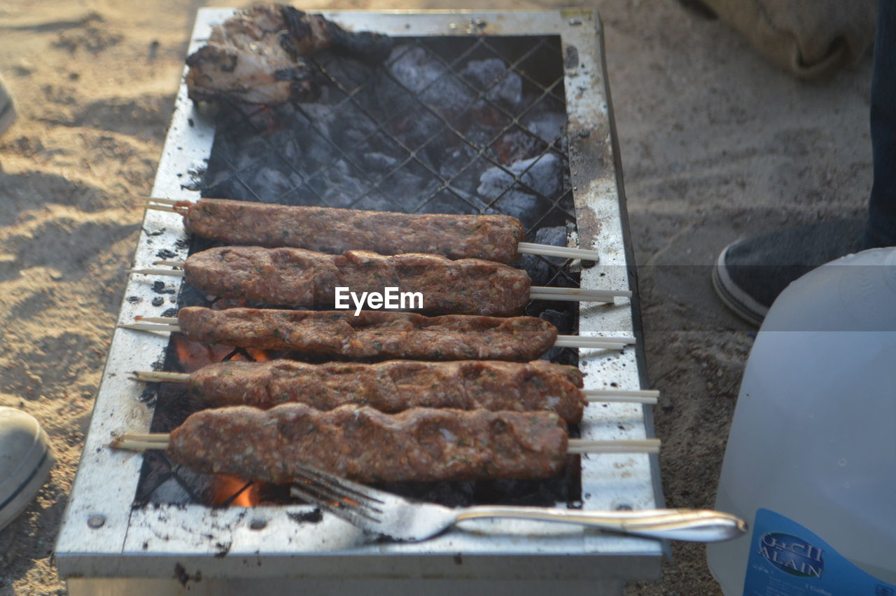 barbecue, barbecue grill, grilled, food and drink, meat, food, preparation, heat - temperature, outdoors, high angle view, freshness, day, no people, serving tongs, metal grate, sausage, close-up