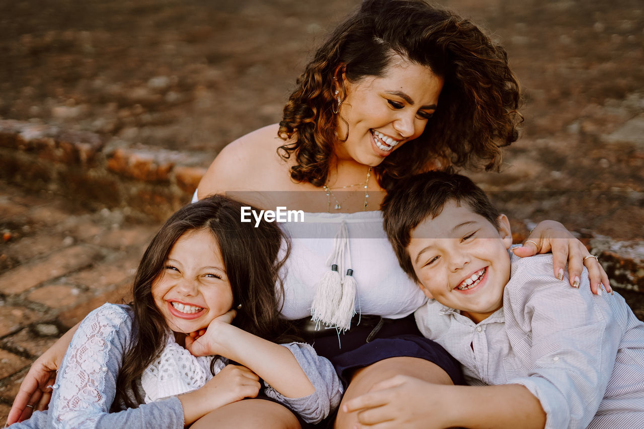 Close-up of smiling mother with son and daughter against building