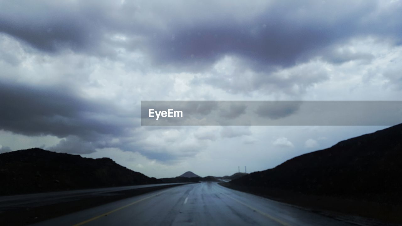 road, transportation, cloud - sky, the way forward, sky, scenics, nature, landscape, no people, outdoors, tranquil scene, tranquility, dividing line, day, storm cloud, beauty in nature, mountain, car point of view