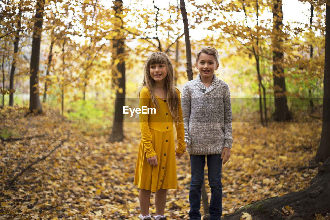 autumn, tree, togetherness, women, looking at camera, portrait, casual clothing, smiling, standing, two people, yellow, bonding, real people, emotion, change, leisure activity, plant, front view, young adult, females, outdoors, daughter, positive emotion, hairstyle