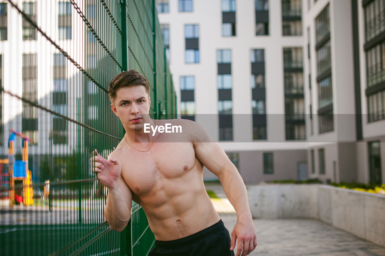 Portrait of muscular man standing by fence at park
