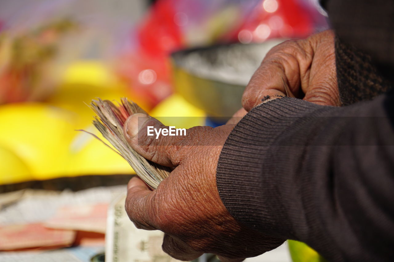 Close-up of man holding paper currency at shop
