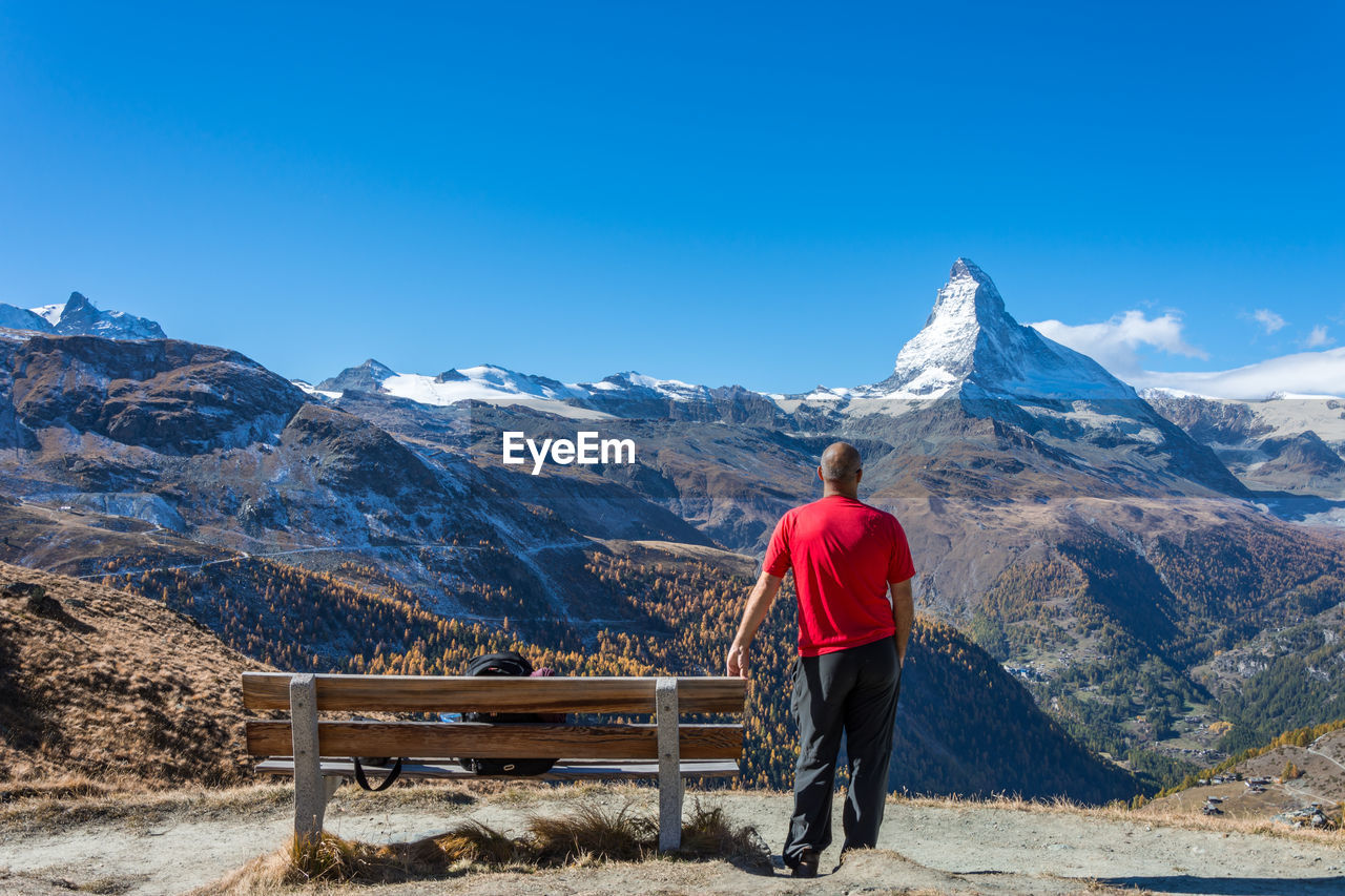 Rear View Of Man Standing Against Snowcapped Mountain And Sky