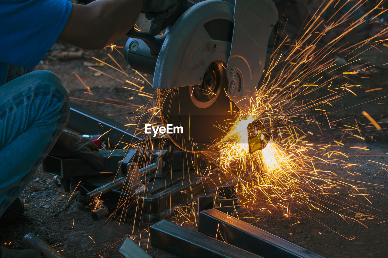 Cropped Image Of Male Worker Cutting Metal In Factory