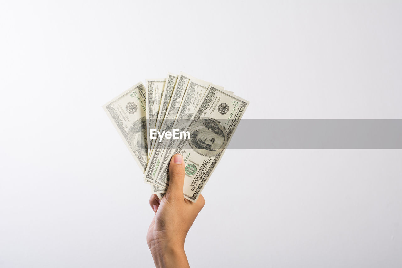 Cropped hand of woman holding us currency against white background