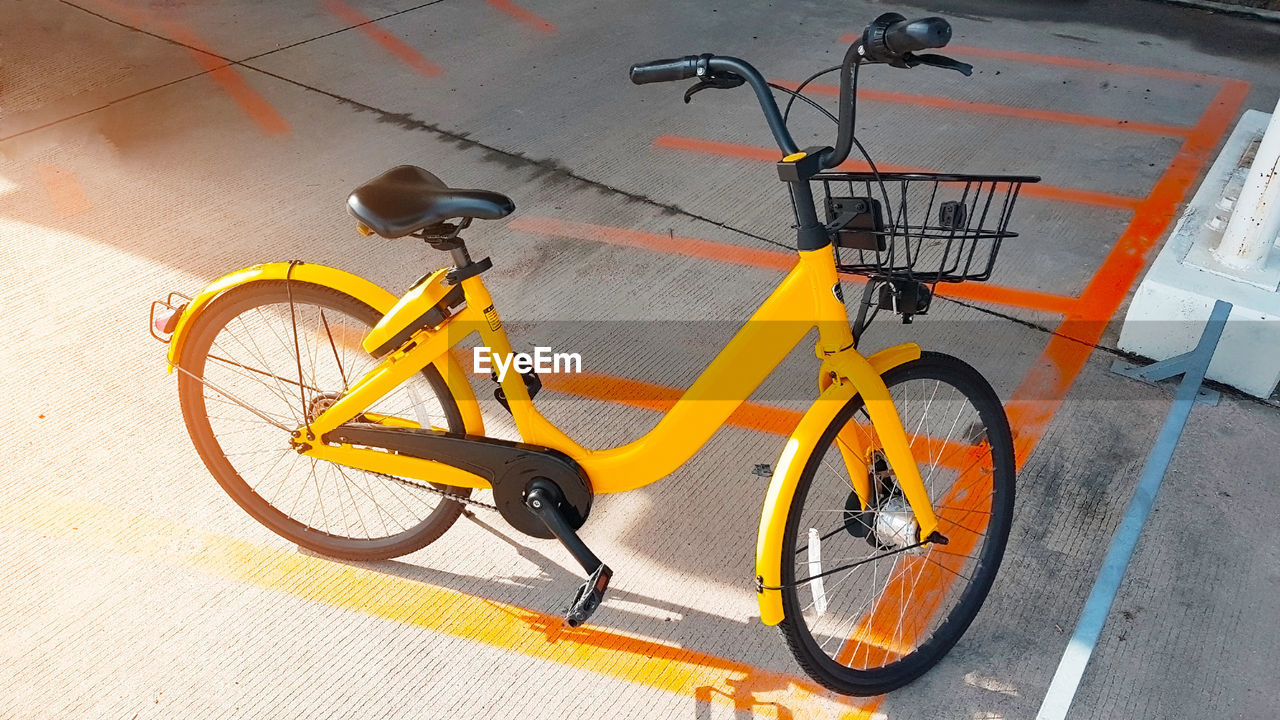 transportation, land vehicle, bicycle, mode of transportation, stationary, high angle view, no people, yellow, day, street, wheel, footpath, city, orange color, scooter, shadow, outdoors, basket, absence, parking