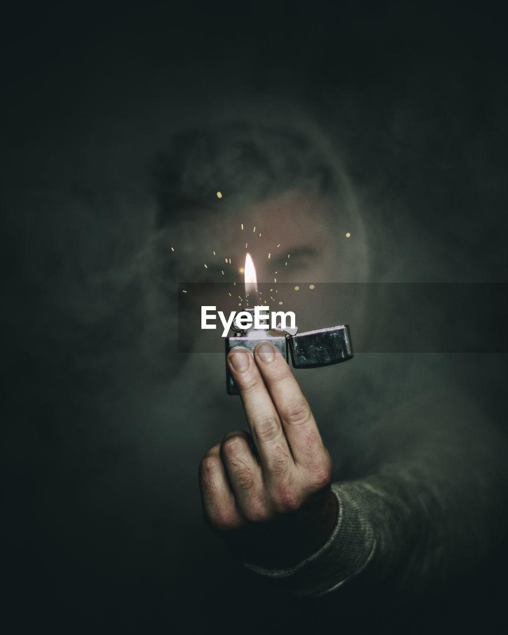 Close-Up Of Man Holding Burning Cigarette Lighter Amidst Smoke