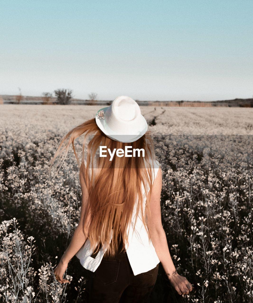 REAR VIEW OF WOMAN IN HAT ON FIELD