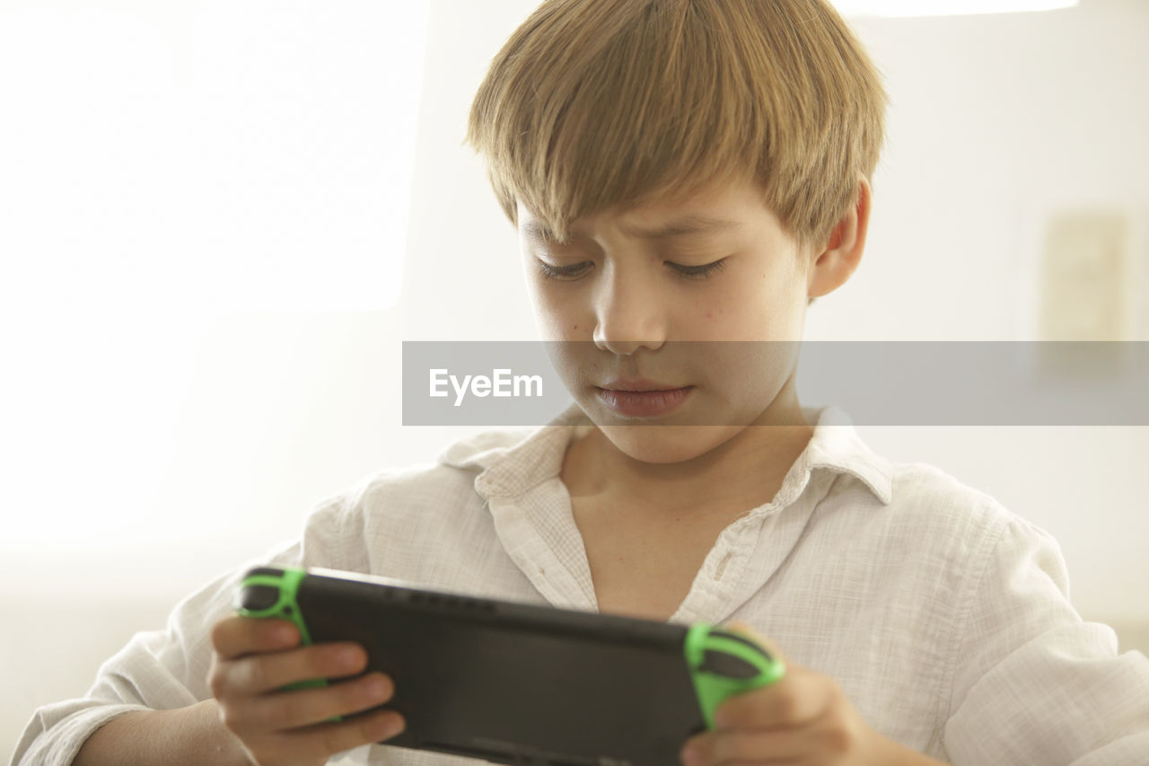 Close-up of smiling boy playing video game at home
